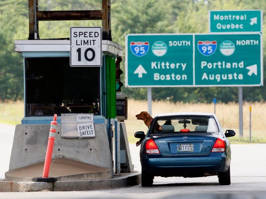 A motorist and her dog wait for change at a toll booth