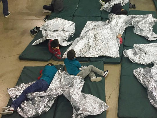 People rest in cages at a detention facility, McAllen,