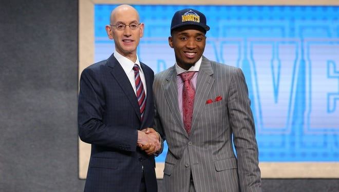 Jun 22, 2017; Brooklyn, NY, USA; Donovan Mitchell (Louisville) is introduced by NBA commissioner Adam Silver as the number thirteen overall pick to the Denver Nuggets in the first round of the 2017 NBA Draft at Barclays Center. Mandatory Credit: Brad Penner-USA TODAY Sports