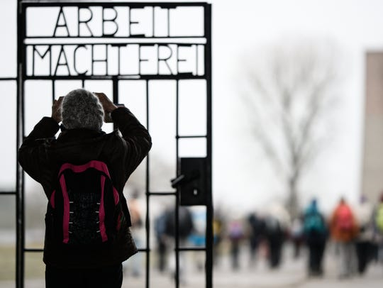 "A visitor takes a photo of the gate that says ""Arbeit"