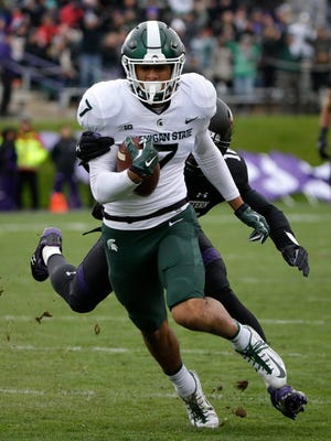 Michigan State receiver Cody White carries the ball past Northwestern safety Godwin Igwebuike in the first half in Evanston, Ill., Saturday, Oct. 28, 2017.