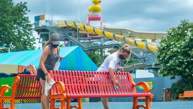 From left, Mollie Nellist, 19, of Levittown, and Rosa Peronace, 22, of Philadelphia, sanitize a bench in preparation for Sesame Place's reopening next week.