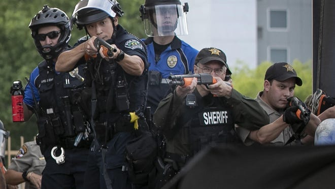 Officers aim into a crowd of protesters outside the Austin Police Department's headquarters on May 30, moments before a woman who said she was pregnant fell to the ground with injuries to her abdomen and back from less lethal rounds. After documenting skull fractures and penetrating wounds, doctors are calling for police agencies across the country to stop using the so-called less lethal ammunition for crowd control.