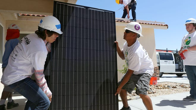 Xavier Villegas of Desert Hot Springs High School's Renewable Energy Academy of Learning, left, and Alberto Panuco of Hot Purple Energy lift a solar panel for installation at a Desert Hot Springs home on Thursday, April 9, 2015. The installation was part of the GRID Alternatives Solarthon.