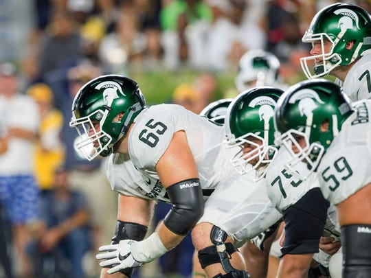 Michigan State's Brian Allen (65) waits to hike the ball against Notre Dame in 2016.