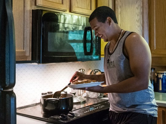 Felix Baez makes a plate of food after preparing a tuna and rice lunch for himself and his roommates, Shane Weedman and Taylor Hillson, at their host Allen Weinbach's kitchen in Evansville, Ind., on Tuesday, Aug. 8, 2017. Baez likes to cook and often brings leftovers to Bosse stadium to share with the other players during practice.