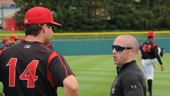 Indianapolis athletic trainer Dru Scott, a Clinton Prairie High School graduate, talks with third baseman Eric Wood (14) prior to a recent batting practice.