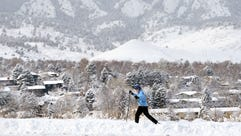 A woman cross country skis amid fresh snow past a residential