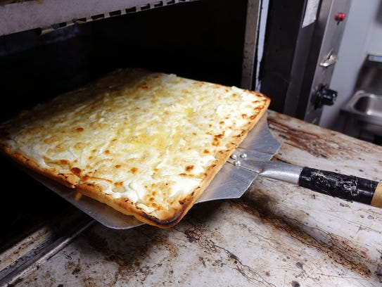 A white pizza is removed from the oven at Crisp Premium