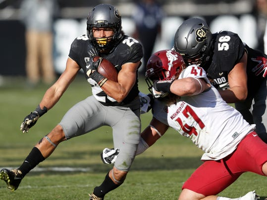 FILE - In this Nov. 19, 2016, file photo, Colorado running back Phillip Lindsay, left, is pulled down by Washington State linebacker Peyton Pelluer in the first half of an NCAA college football game in Boulder, Colo. Colorado is gearing up for another run to the Pac-12 title game as the team's season is set to begin. (AP Photo/David Zalubowski, File)