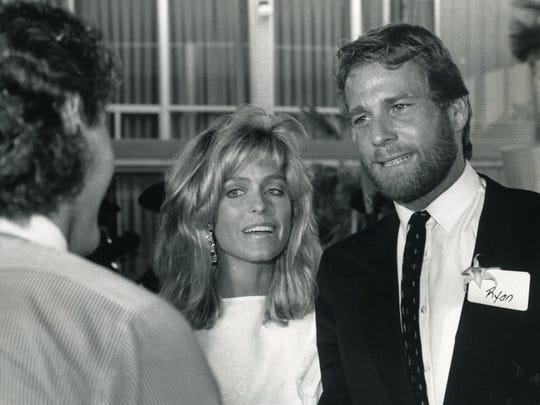 Farrah Fawcett and Ryan O'Neal greet guests at a reception
