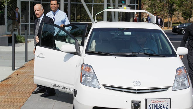 From left, California Gov. Edmund Brown Jr., state Sen. Alex Padilla stand by a driverless car they arrived in at Google headquarters in Mountain View, Calif.