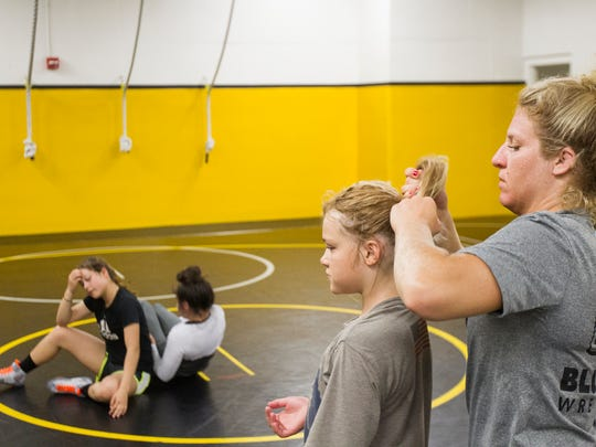 Hawkeye Wrestling Club's Lauren Louive helps Lyniann Gusick, 9, of Center Point, put her hair up during the first Iowa Women's wrestling camp in Iowa City at the Dan Gable Wrestling Complex on Monday, July 9, 2018.
