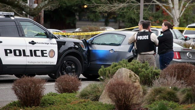 A Bainbridge Island Police vehicle is seen pressed up against a gray ford mustang at the scene of an officer involved shooting in front of Winslow Green on Bainbridge Island on Wednesday, Feb. 7, 2018.