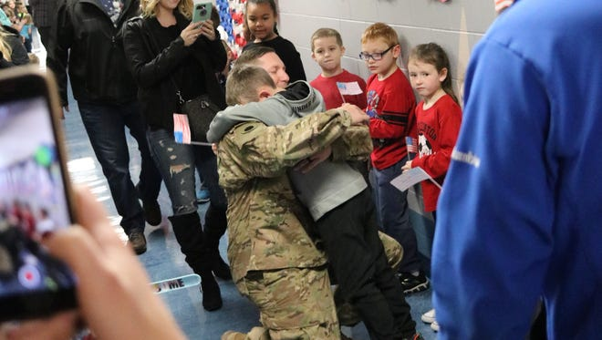 U.S. Army Spc. Marz Rickey embraces his two sons, Damian and Noah, at Bataan Memorial Primary School on Thursday, after having been deployed overseas for much of the past year.