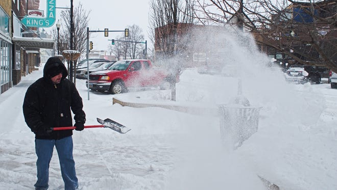Rob Souhrada, of Brookings, S.D., shovels snow outside his apartment in downtown Brookings Sunday, March 12, 2017,   during a winter storm.
