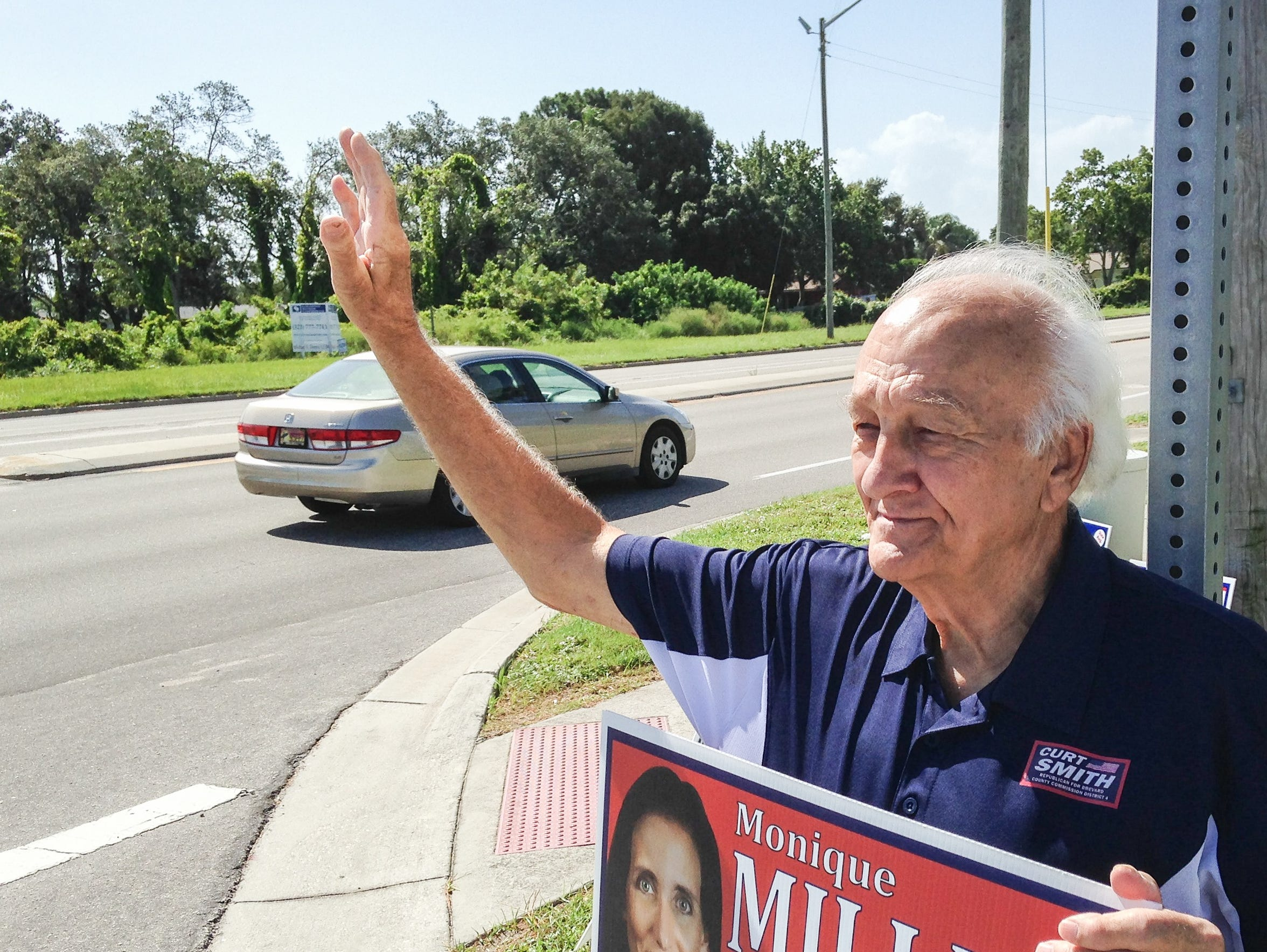 Candidate supporter Dale Young waves to motorists on Wickham Road during one of the most recent elections.