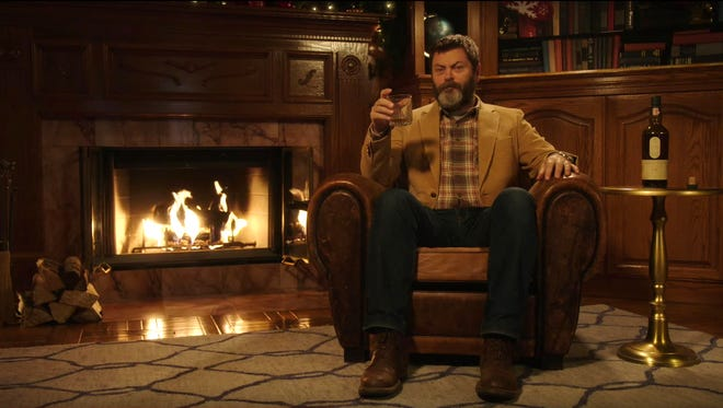 Nick Offerman sips scotch by the fire for 45-minutes straight in a new virtual Yule Log video on YouTube.