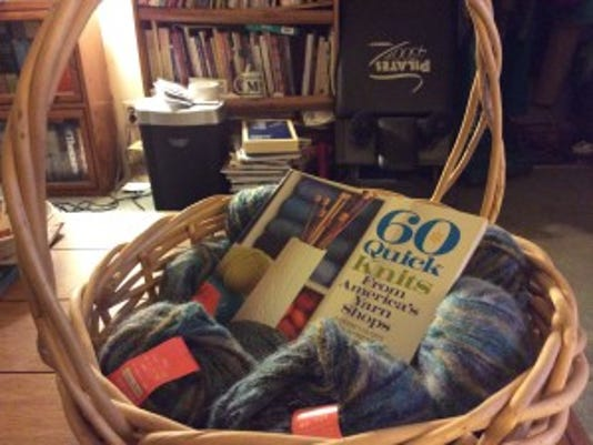 Here's the gift basketk with my donations of yarn and a book. In the background, you can see the bookcase and the pile of books that won't fit in it.