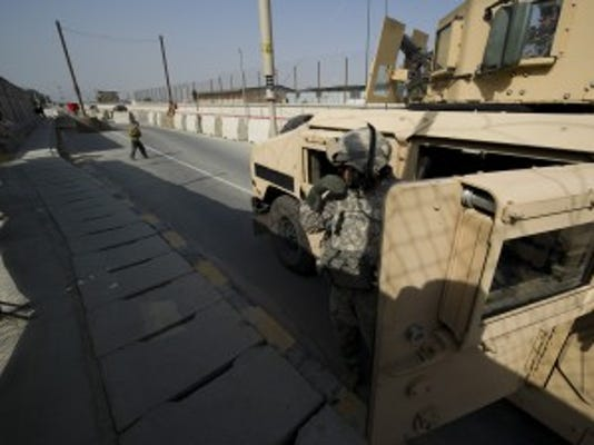 Vermont National Guard Soldier Sgt. 1st Class Harwood of Argyle, NY, steps out from his armored HumVee to check on a child who was begging for money outside of the military gate to the Kabul International Airport on Thursday, September 9, 2010. RYAN MERCER, Free Press
