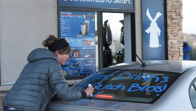 Amy Hardesty writes on a customer's car at Dutch Bros. Coffee Fort Collins' on opening day, Wednesday, December 28, 2016. The drive-thru coffee shop gave away free coffee all day.