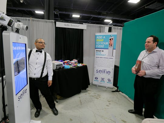 Stobie Gerena of Lakewood, a photo booth attendant, demonstrates the Selfie Terminal, a company based in Lakewood, by taking a selfie of Phil Brach of Flatbush, NY, sales manager of Jewish Echo magazine, during JBIZ Expo and Conference at the New Jersey Convention and Exposition Center in Edison, NJ Wednesday June 1, 2016.