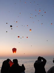 Friends and family release paper lanterns in memory