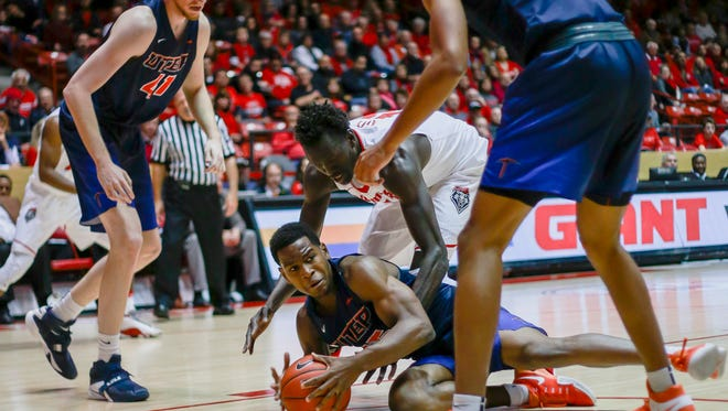 UTEP's Dominic Artis scrambles for a loose ball  while guarded by New Mexico's Obij Aget, flanked by UTEP's Matt Willms, left, and Paul Thomas during the first half their game basketball game Wednesday in Albuquerque. UNM edges the Miners 78-77.