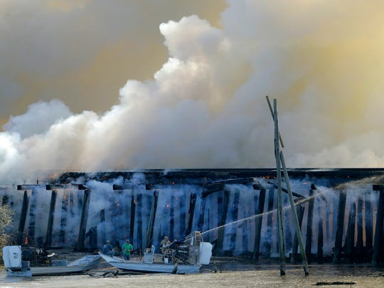 A fire burns on a train trestle parallel to Interstate
