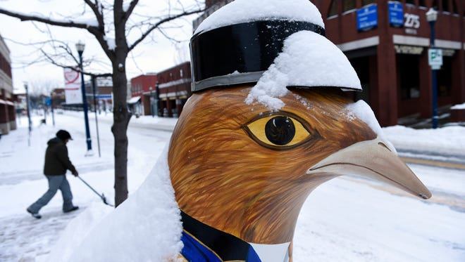 A worker clears the sidewalk near a chicken sculpture in Annapolis, Md., Tuesday, Feb. 17, 2015, after several inches of snow closed the federal government and schools.