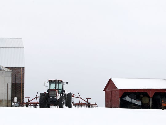 A tractor stands idle in the snow on a farm near Slater in this file photo from May 2013.