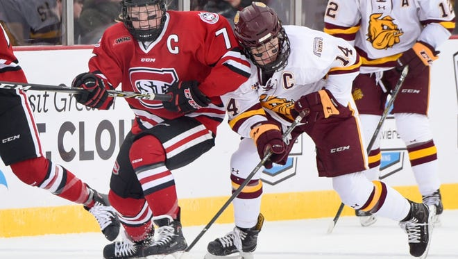 St. Cloud State's Brittney Anderson and University of Minnesota-Duluth's Sydney Brodt battle for the puck during the first period Saturday, Jan. 20, during Hockey Day Minnesota at Lake George.