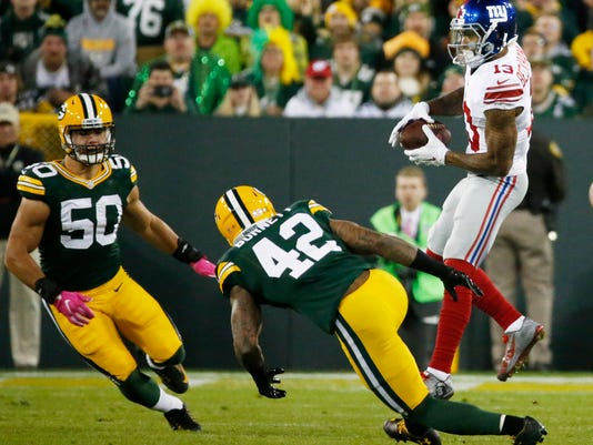 New York Giants' Odell Beckham catches a pass in front of Green Bay Packers' Blake Martinez (50) and Morgan Burnett (42) during the first half of an NFL football game Sunday, Oct. 9, 2016, in Green Bay, Wis. (AP Photo/Mike Roemer)