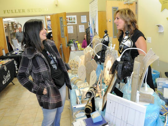 Laura D'Urso (right), who sells Touchstone Crystal by Swarovski jewelry, speaks with Helaine Conti of Marlboro at Phoenix Productions Holiday Bazaar in Red Bank.