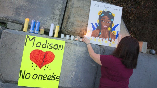 Denice Dato adjusts a piece of art depicting Madison Meredith Saling at an event remembering her life on Saturday, June 16.