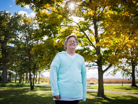 Ena Hollowell, who has Stage 4 breast cancer, stands