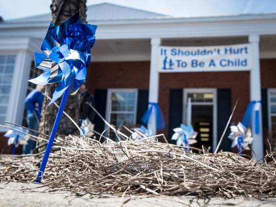 Blue pinwheels spin in the wind as part of a campaign