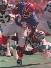 Thurman Thomas is tripped up by Carolina's Chad Cota during a 1995 game.