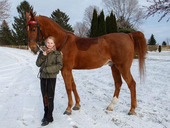 National equestrian champion Hadley Novak walks with