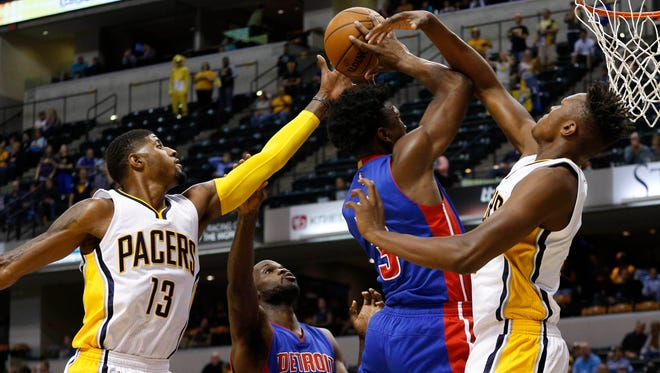 Detroit Pistons forward Stanley Johnson (3) takes a shot against Indiana Pacers forward Paul George (13) and center Myles Turner (33) at Bankers Life Fieldhouse.
