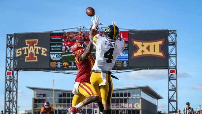 Iowa's (4) Tevaun Smith (4) pulls in a touchdown pass in front of Iowa State's (10) Brian Peavy during the first half of their football game Saturday Sept. 12 2015, at Jack Trice Stadium in Ames, Iowa.