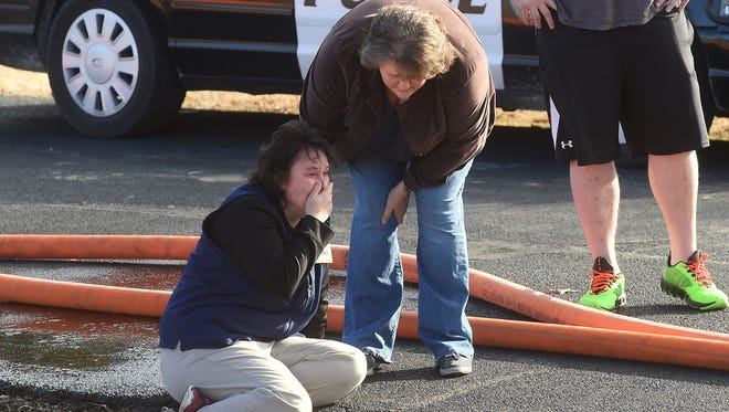 A friend comforts Jennifer Gorbet, left, as her Gassville home burns on Wednesday morning. The home was a complete loss. No injuries were reported.