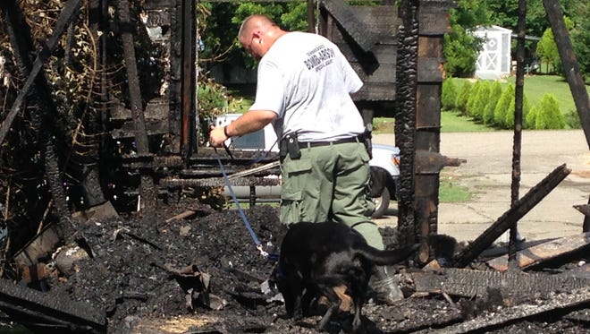 ATF-trained accelerant-detecting dog Wrigley assists with the investigation of a fire at Fruitland Presbyterian Church. The canine handler is from the Tennessee State Fire Marshal's Office.