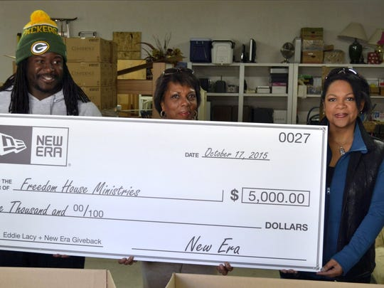 With the help of Green Bay Packers running back Eddie Lacy, New Era Cap Co. donated $5,000 as well as food and clothing to Freedom House Ministries in Green Bay on Saturday. From left are Lacy, are Freedom House executive director Robyn Davis and development coordinator Melissa Hyska.