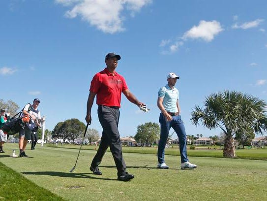 Tiger Woods, center, and Sam Burns, right, walk off