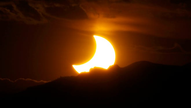 In this May 20, 2012, file photo, a solar eclipse is seen from downtown Denver as the sun sets behind the Rocky Mountains.