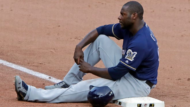The Brewers' Lorenzo Cain sits on third base during a pitching change in the ninth inning.