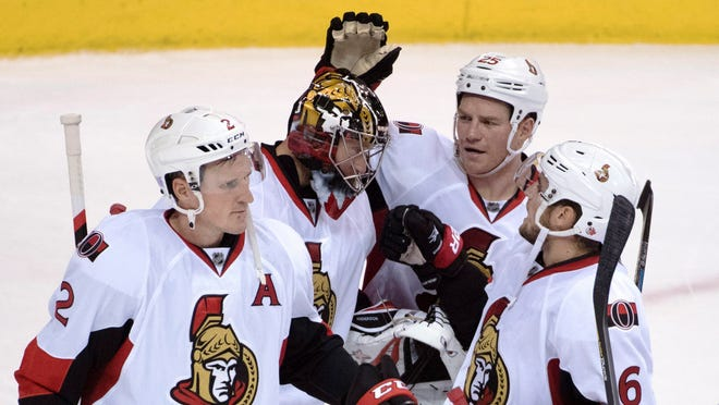 Ottawa Senators' Dion Phaneuf (2), left to right, goalie Craig Anderson (41), Chris Neil (25) and Chris Wideman (6) celebrate their victory over the Vancouver Canucks following the third period of an NHL hockey game, Tuesday, Oct. 25, 2016 in Vancouver, British Columbia.  (Jonathan Hayward/The Canadian Press via AP) ORG XMIT: JOHV117