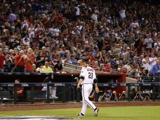Zack Greinke walks off the field in the sixth inning