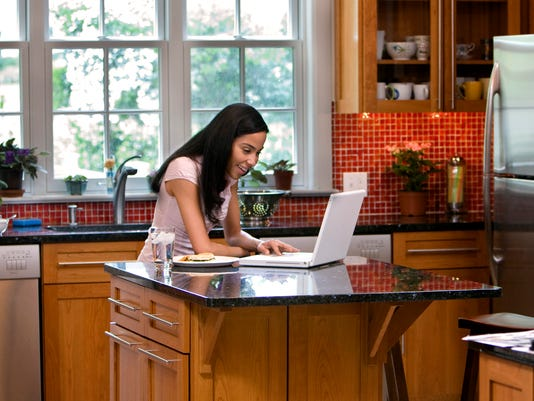 Woman in kitchen on laptop